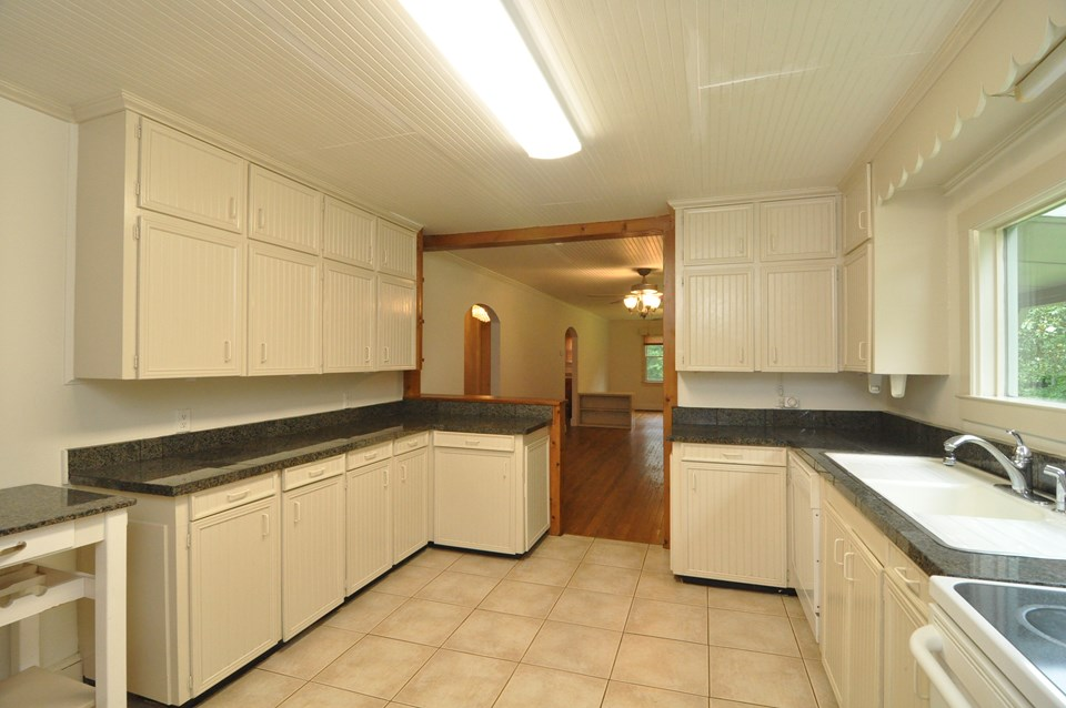 kitchen the kitchen is 14 x 11.8 with plenty of cabinet space, a granite tile counter top, movable kitchen island, tile floor and bead board ceiling.  there is a dishwasher, electric range and refrigerator.