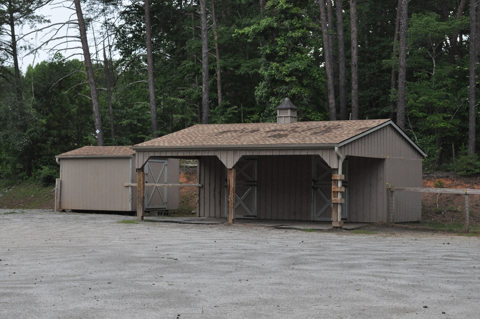 shed row style barn the barn is 24 x 21 with two 12 x 10 stalls with dutch doors and an overhang.  stalls and porch area have mats.  feed and tack shed is 12 x 10.  there is power to both structures, but no water.  the barn opens to the riding ring which also doubles as a dry lot so the horses can go in and out at will if desired.